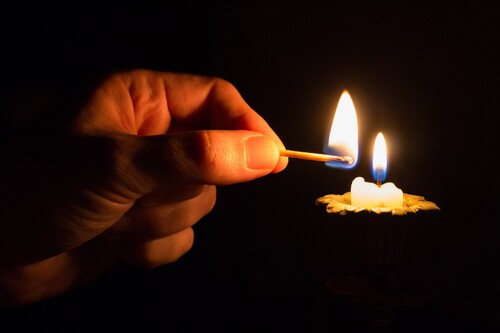 person-holding-match-stick-with-fire-in-front-of-candle-with-fire.jpg